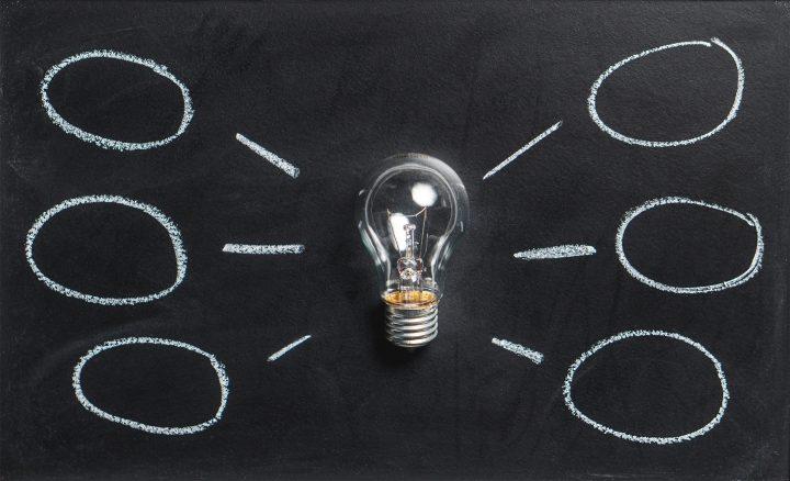Glühbirne auf Tafel mit angezeichneten Denkblasen drum herum