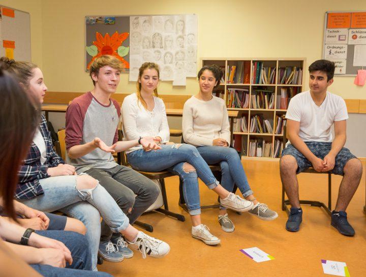 Schüler*innen sitzen in einem Stuhlkreis und diskutieren